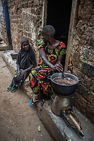 Uganda, Kikandwa. Eunice  Babirye (27), is married with six children. Over 30 family members live in her housing compound. She uses the BioLite stove for cooking because it emits less smoke as well as charges light,  a radio and her mobile phone. Using the BioLite stove, cooking with her children.
