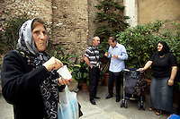 """Italy. Lazio region. Tivoli. Several people, all romanian citizens, talk together after the orthodox sunday mass. An old woman eats Koliva (Romanian, colivă ) in a white plastic glass. While recipes may vary widely, the primary ingredient of Koliva is wheat kernels, which have been boiled until they are soft, and then sweetened with honey, sugar, and some fruit. It may also contain sesame seeds, almonds, ground walnuts, cinnamon, sugar, pomegranate seeds, raisins, anise and parsley. Romanians also decorate the koliva with crosses of cocoa, chocolate or candy. The orthodox religious service took place in a catholic church """" Chiesa di San Pietro alla Carita"""". Romanian immigration. Tivoli is a town and comune in the province of Rome.  02.10.2011 © 2011 Didier Ruef"""
