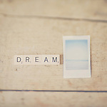 a retro instant photograph of the ocean with the word dream in scrabble tiles