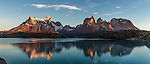 Panoramic sunrise view of the Paine Massif with reflections.  Left to right - Cerro Paine Grande, the Cuernos del Paine, or Horns, and Monte Almirante NIeto.  Lake Pehoe is in the foreground.  Taken from Hosteria Pehoe island.  Torres del Paine National Park in Patagonia, Chile.  A UNESCO World Biosphere Reserve.