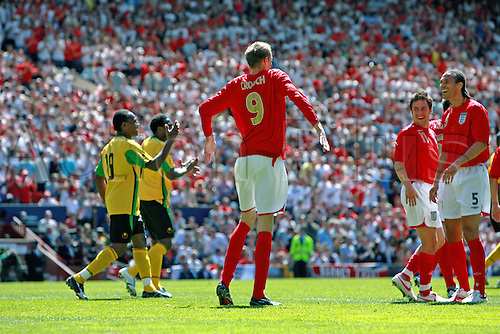 3 June 2006: England striker Peter Crouch does his robot celebration in front of his teammates after scoring England's third goal during the International Friendly match between England and Jamaica played at Old Trafford, Manchester. England won the game 6-0. Photo: Steve Bardens/actionplus...060603 soccer football man men male celebrate celebration joy team mate