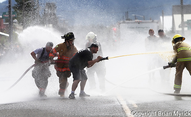 Members of the Cle Elum and Roslyn fire departments engage in a traditional water fight during the Pioneer Days parade through downtown Cle Elum, Saturday, June 30, 2012. (Brian Myrick / Daily Record)