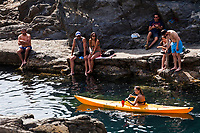 A sea kayaker paddling by the croud of sun bathers on the rocks of Manarola Harbor in Cinque Terre Italy