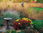Bureau, County, IL<br /> Birdbath and garden of fall flowers at the edge of a tall grass prairie