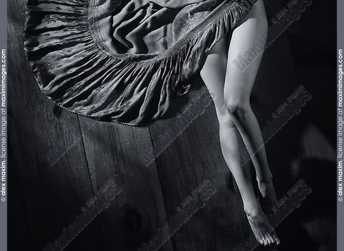 Sensual artistic portrait of sexy woman legs and a dress on wooden floor Black and white