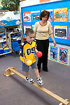 Berkeley CA  Teacher studing preschool student's balancing skills in class.