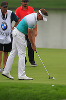 Ian Poulter (ENG) taps in on the 11th green during Friday's Round 2 of the 2014 BMW Masters held at Lake Malaren, Shanghai, China 31st October 2014.<br /> Picture: Eoin Clarke www.golffile.ie