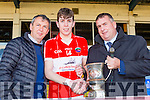 Countyboard chairman Patrick O'Sullivan and Peter Keane presents Daingean Uí Chúis captain and Man of the Match Conor Geaney the County Minor championship cup after defeating Mid Kerry in the final in Fitzgearald Stadium on Sunday