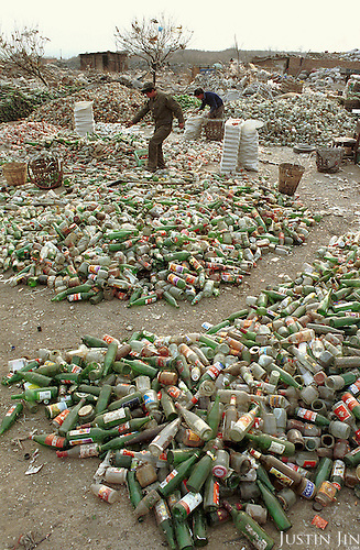 A man walks past recycled bottles in garbage dump in Beijing..Picture taken March 1999.Copyright Justin Jin