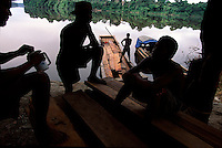 "Loggers unload a boat of Greenheart and purpleheart timber at Rockstone landing, guyana.  They had to bail the boat all night to keep it afloat.  These amerindians are called ""pokenockers"" because they poke around here, knock around there trying to make a little bit of money.  They travel the trails that trace the interior of Guyana all the way to the ""back door"" of Brazil."