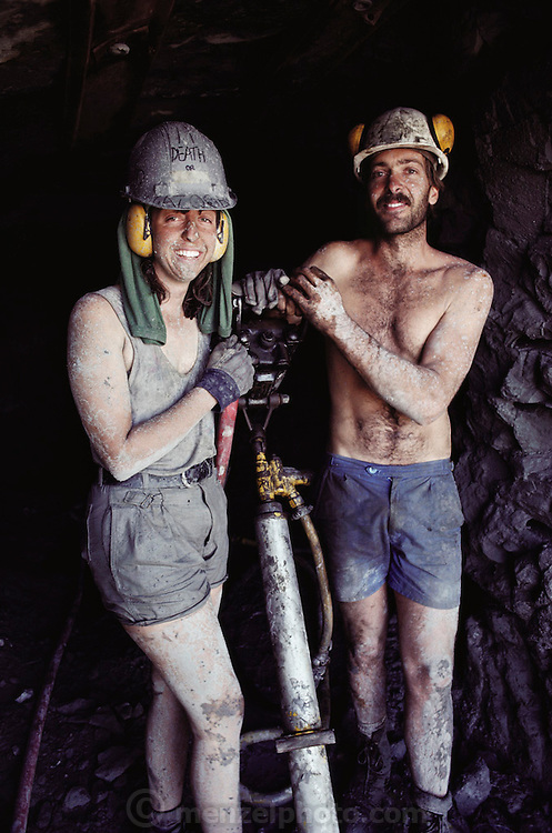 Newlyweds Helen and John Wilson after a hard day of drilling and jack hammering at Dinosaur Cove. They are members of the Dinosaur Cove excavation team that is drilling holes in the working face of the mine to allow explosives to be placed. The explosives are used to dislodge large pieces of rock, which are then removed and checked for fossil remains. Dinosaur Cove, near Cape Otway in southern Australia, is the world's first mine developed specifically for paleo-ontological excavations. MODEL RELEASED [1989]