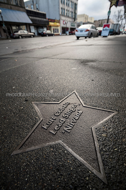 2/20/2014&mdash;Aberdeen, WA, USA<br /> <br /> A star for Kurt Cobain on Wishkah Street in Aberdeen, WA. Many homeless and drug addicts frequent this stretch of downtown Aberdeen.<br /> <br /> Aberdeen, located in Grays Harbor County, near the Washington State coast,  is the birth place of rock legend Kurt Cobain, lead singer of Nirvana. Aberdeen and the neighboring town of Hoquiam, have had a difficult relationship with Cobain&rsquo;s legacy, with his drug use and suicide causing many in the community to believe he should not be honored. In recent years though, as the 20th anniversary of Cobain&rsquo;s death approaches and Nirvana is set to join the Rock and Roll Hall of Fame, a steady stream of tourists and travelers are coming to the town to see Cobain&rsquo;s childhood home and other sights. Many in Aberdeen &ndash; a place Cobain once mocked as &ldquo;Twin Peaks without the excitement&rdquo; &ndash;  are now embracing him and the city held its first annual Kurt Cobain Day on Thursday, February 20th, 2014.<br /> <br /> Aberdeen though, has fallen on hard times. With the slow death of the logging and fishing industries, its downtown is filled with abandoned shops, storefront churches and a steady stream of drug addicts, homeless kids and prostitutes. Most cars pass through the city&rsquo;s main street, Wishkah Street, without stopping, heading to resort hotels and vacation homes on the Washington coast. Unemployment is high, many homes are falling down or abandoned.<br /> <br /> Photograph by Stuart Isett<br /> &copy;2014 Stuart Isett. All rights reserved.