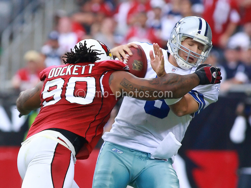 Oct 12, 2008; Glendale, AZ, USA; Dallas Cowboys quarterback Tony Romo (8) is sacked by Arizona Cardinals defensive tackle Darnell Dockett (90) in the first half of a game at Univeristy of Phoenix Stadium. Romo would lose the ball on the play and the ball was recovered by the Cardinals defense for an apparent touchdown. After review by the officials the play was ruled an incomplete pass. The Cardinals won the game 30-24 in overtime on a blocked punt recovery for a touchdown, the first such victory in NFL history.