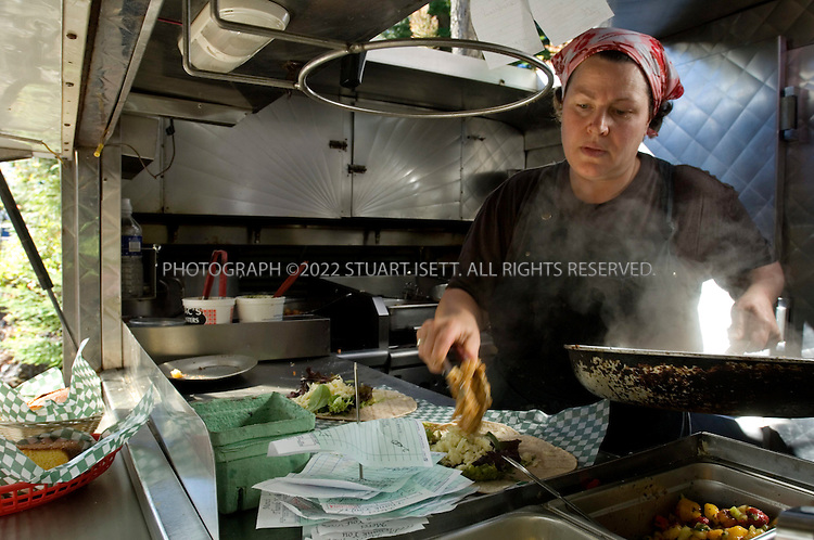 9/24/2006--Tofino, British Columbia, Canada..Texan Lisa Ahier prepares food at her famous SoBo lunchtruck which operates in the Tofino Botanical Gardens,  outranked restaurants four times the price in the latest Zagat survey. The restaurant is run by Texan, Lisa Ahier...Photograph By Stuart Isett.All photographs ©2006 Stuart Isett.All rights reserved.