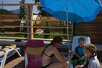 Switzerland. Canton Ticino. Tenero. Camping Campofelice. A mother plays cards with her two children under a blue umbrella on the pool side. Another young woman is lying on a deck chair and sunbathes. Tourists have the opportunity to rent private bungalows, called Igloo Tube Home. The innovative bungalows are made of wood and have electricity from solar energy. A swiss flag is hanged on the igloo. The flag of Switzerland consists of a red flag with a white cross (a bold, equilateral cross) in the centre. It is one of only two square sovereign-state flags. 19.07.2018 © 2018 Didier Ruef