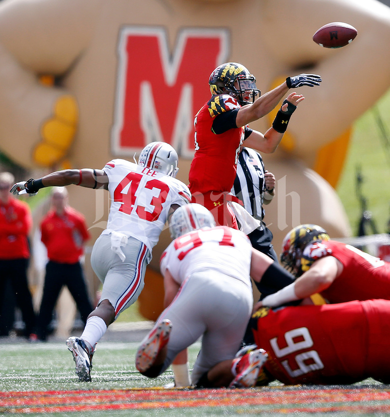 Ohio State Buckeyes linebacker Darron Lee (43) and defensive lineman Joey Bosa (97) put pressure on Maryland Terrapins quarterback C.J. Brown (16) as he releases the ball during the second quarter of the NCAA football game at Byrd Stadium in College Park, Maryland on Oct. 4, 2014. (Adam Cairns / The Columbus Dispatch)