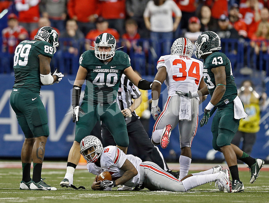 Ohio State Buckeyes quarterback Braxton Miller (5) gets tackled by Michigan State Spartans linebacker Max Bullough (40) in the 2nd quarter during the Big 10 Championship game at Lucas Oil Stadium in Indianapolis, Ind on December 7, 2013.  (Dispatch photo by Kyle Robertson)