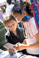 Hmong Children hold money deciding on purchase at concession stand. Hmong Sports Festival McMurray Field St Paul Minnesota USA