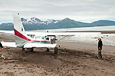 ALASKA, Homer, a woman stands next to a small plane after landing at Hallow Bay, Katmai National Park, Katmai Peninsula, Gulf of Alaska