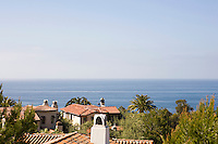 View over the terracotta tiled rooftops to the Pacific ocean from the bedroom balcony