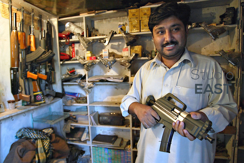 A gunsmith shows off a self designed firearm in his workshop in Pakistan's North West Frontier Province town of Darra Adam Khel, Pakistan, Thursday, October 19, 2006. Darra is a dusty, Wild West-type town, crawling with intelligence agencies, drug smugglers and gun-toting Pathan tribesmen. Darra-built Kalashnikovs, not known for their durability, sell for US$30 to US$45 alongside knuckledusters, shotguns with telescopic sights and twelve bores made to look like M16 assault rifles. Much of the weaponry is made from scrap metal from shipyards. Pakistan's government's attempts to regulate the Darra weapon industry always ended in failure. Photo by Simon Lim/Pictobank.