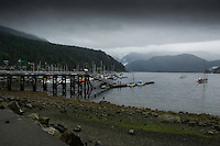 Jetty in Deep Cove Bay with clouds above the mountains over Mount Seymour provincial park. Deep Cove, Burrard Inlet, Vancouver, British Columbia, Canada.