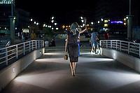 Senigallia, Agosto 2013. Una ragazza vestita stile anni 60 cammina sul lungomare di Senigallia durante il Festival Summer Jamboree.