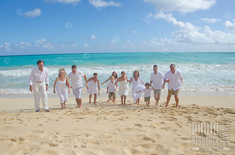 A playful extended family of 11 running towards the photographer on sunny Waimanalo Beach, O'ahu.
