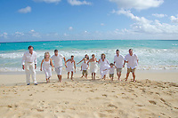 A playful extended family of 11 running towards the photographer on sunny Waimanalo Beach, O'ahu.