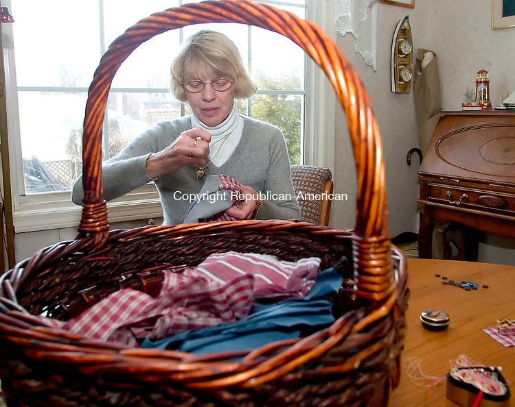 WATERBURY, CT- 05 MARCH 06- 030507JT04- <br /> With a basket of scraps in the foreground, Marjorie Czarsty sews a button onto a skirt she is making with her late husband's shirts in her Waterbury home. Czarsty's husband, Ron, died in November, and she couldn't bring herself to throw out his shirts. She says the skirts are her way of grieving and staying close to the love of her life.<br /> Josalee Thrift Republican-American