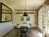 The dining room is furnished with a contemporary table and chairs and a collection of model houses is displayed on one wall