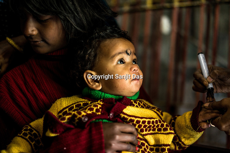 An infant gets his finger marked after getting the oral vaccination at a polio booth during Polio Day at a municipal office in Kolkata, West Bengal, India.<br /> On Polio Days, small booths are set up in different parts of the city, urging local residents to vaccinate their children below 5 years.