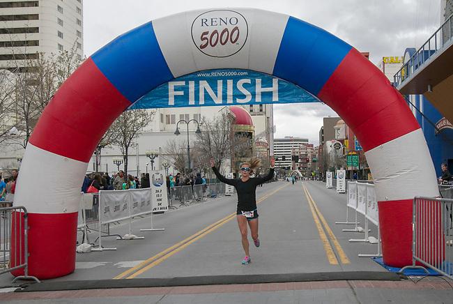 Half Marathon winner Elizabeth Lyles crosses the finish line during the 6th Annual Reno 5000 Downtown River Run on Saturday, April 6, 2019.