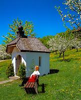 Deutschland, Bayern, Oberbayern, Chiemgau: Frau ruht auf Bank vor Kapelle, Blumenwiese und Apfelbluete | Germany, Bavaria, Upper Bavaria, Chiemgau: woman sitting on bench, chapel, flower meadow and fruit tree blossom