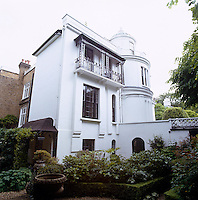 The exterior of the white villa with its black wrought-iron balcony and distinctive turret