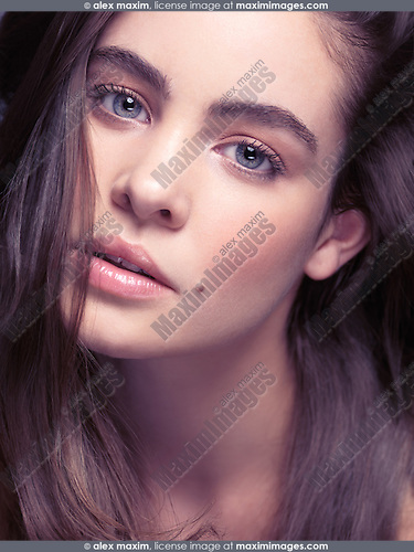 Close up of young woman face with beautiful gray eyes and bushy eyebrows