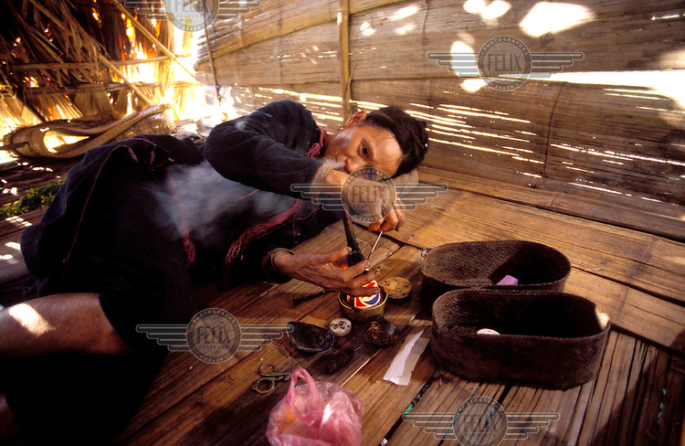 © Chris Stowers / Panos Pictures..LAOS..Tribal woman smoking opium.