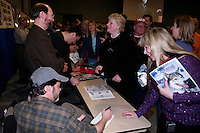Bob Bundtzen (standing) and Bruce Linton ( sitting ) sign autographs for race fans at the musher's banquet in Anchorage, Alaska  2009 Iditarod