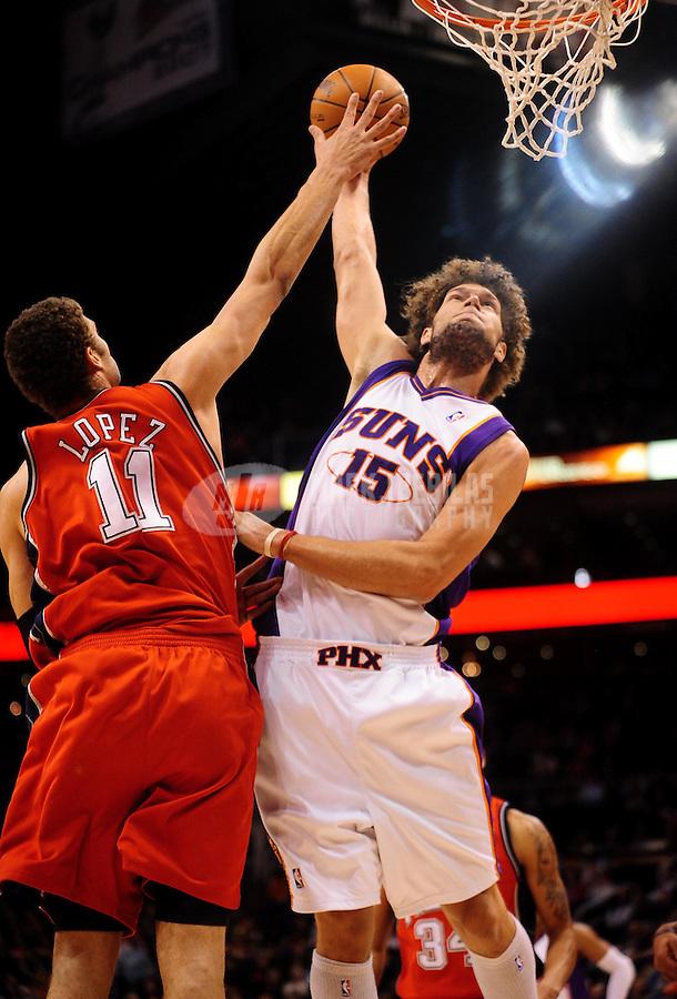 Jan. 20, 2010; Phoenix, AZ, USA; Phoenix Suns center (15) Robin Lopez dunks the ball above brother New Jersey Nets center (11) Brook Lopez in the first half at the US Airways Center. Mandatory Credit: Mark J. Rebilas-
