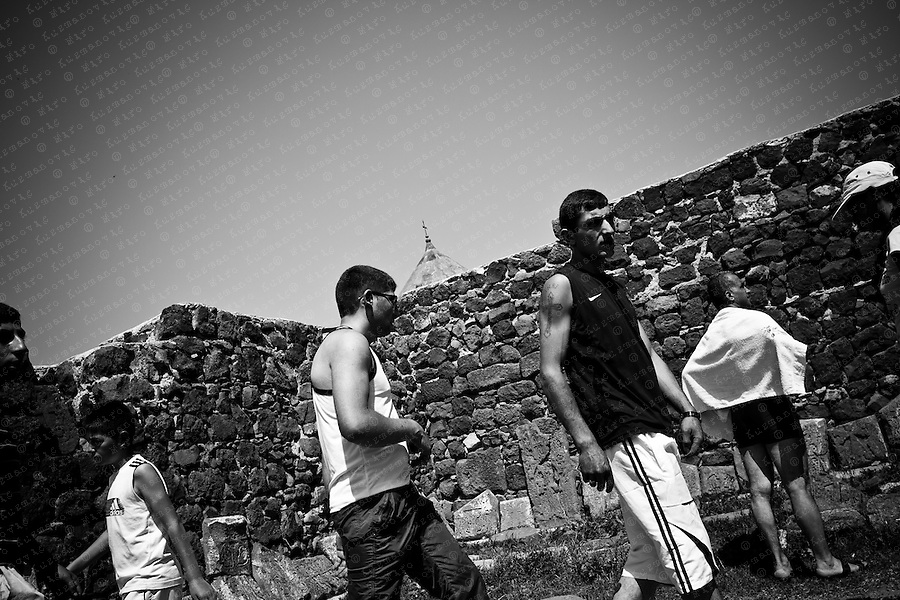 Tourist and Pilgrims walk next to broken khachkar (carved cross-stone), one of the most characteristic symbols of Armenian identity, at the Sevanavank, a monastic complex located on a peninsula at the shore of Lake Sevan. A number of khachkars, which were created in historic Armenia and surrounding regions, in modern times have become the possession of Turkey, Azerbaijan, and partly Georgia and Iran. The khachkars were broken into pieces or were transformed to stones for construction and were used in the construction of individual houses and public buildings, particularly in the walls of public schools.