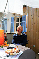 Bertrand Dessane pictured relaxing at a table on the roof terrace of his apartment
