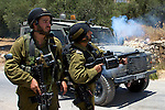 An officer in the IDF uses a grenade launcher to fire CS gas at Palestinian youths (unseen) that were throwing rocks following a nonviolent demonstration against Israel's controversial separation barrier in the West Bank town of Beit Jala near Bethlehem on 27/06/2010.
