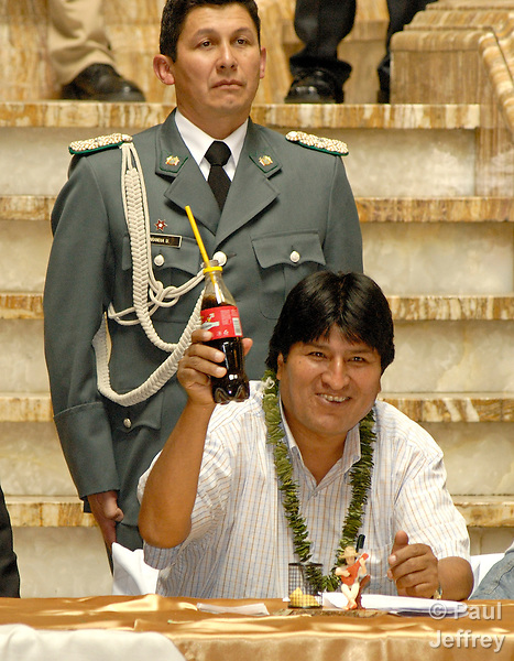 Evo Morales, the first indigenous president of Bolivia. An Aymara, Morales took office in January 2006. Here he salutes a group of students having lunch at the National Palace. He is wearing a necklace of coca leaves and drinking Coca-Cola.
