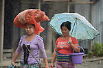 Women walk in the rain in Tuingo, an ethnic Chin village in Myanmar.