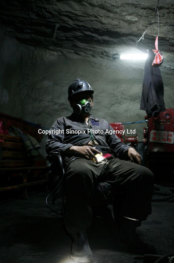 A coal miner wearing a mask takes a break from work at one of the state-owned mines near Luoyang, Henan Province, China..