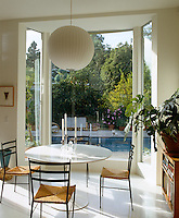 A floor-to-ceiling bay window ensures maximum light in this simple and elegant dining room which overlooks a large outdoor swimming pool