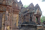 Angkorian temple Banteay Srei (late 10th century) 967.<br /> Eastern face of the southern library on left.Main entrance to mandapa and central sanctuary tower with gaurdians.<br /> The central sanctuary and the southern sanctuary were dedicated to Shiva and the northern sanctuary was dedicated to Vishnu.<br /> Banteay Srei temple is situated 20km north of Angkor, built during the reign of Rajendravarman by Yajnavaraha, one of his counsellors. In antiquity Isvarapura was a small city that grew up around the temple. Banteay Srei was dedicated to the worship of Shiva, the foundation stele describes the consecration of the linga Tribhuvanamahesvara (Lord of the three worlds) in 967.