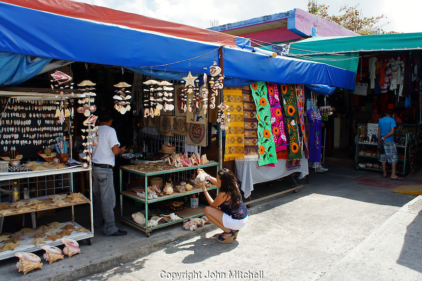 Young woman tourist looking at seashells, Mexican handicrafts in Mercado 28 souvenirs and handicrafts market in  Cancun, Mexico      .