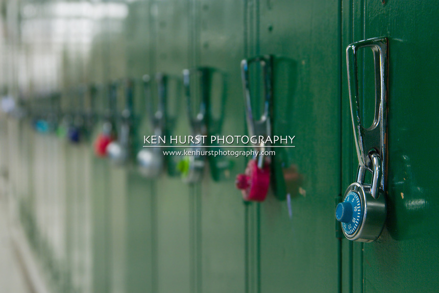 Closeup view of a lock on a school locker with row of lockers in background out of focus from depth of field.