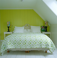 In the bedroom bright lime green weaves its way through the patterned bedspread and the lampshades to the painted tongue-and-groove wall behind